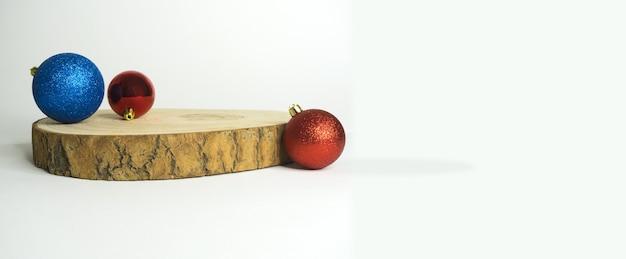 Holzscheit mit einfachen weihnachtskugeln und weißem hintergrund