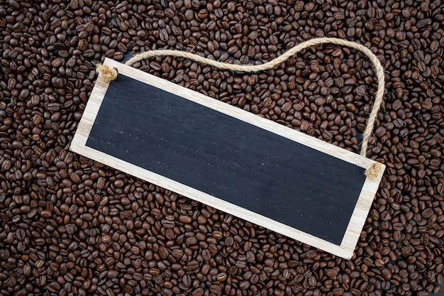 Holzschild heißen kaffee und bohnen auf holztischhintergrund