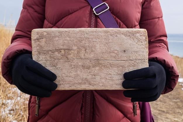 Holzschild oder -tafel in weiblichen händen als layout für den nachrichtentext. trampen, bitte, gratulation, warnung oder nachricht
