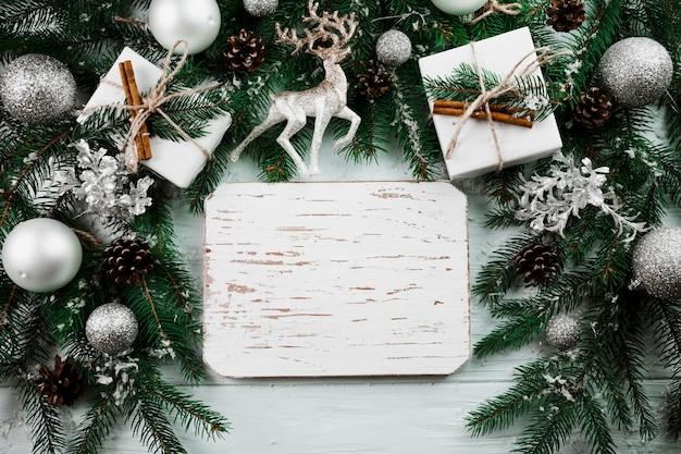 Holzschild zwischen weihnachtszweigen