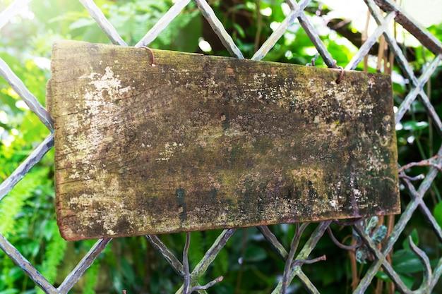 Holzschildbrett, das am stahlzaun hängt