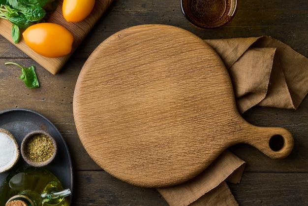 Holzschneidebrett auf dunklem hintergrund kochen vorbereitung gemüse und gewürze