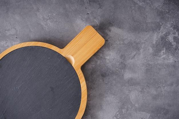 Holzschneidebrett auf grauem hintergrund, platz für text. draufsicht.