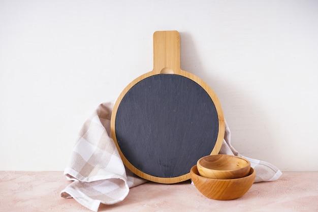 Holzschneidebrett mit einem küchentuch auf einem beigen hintergrund, mit platz für text.