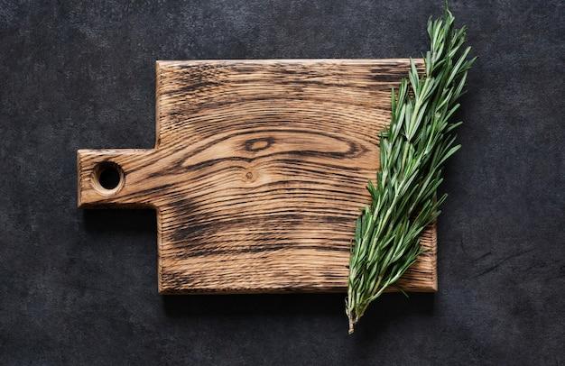 Holzschneidebrett mit frischem rosmarin auf einem schwarzen betontisch. draufsicht mit kopierraum.