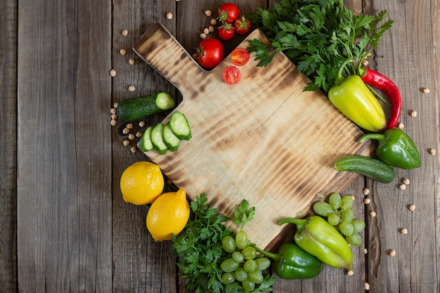Holzschneidebrett mit frischen kräutern, rohem gemüse und früchten auf rustikaler hölzerner tischoberansicht