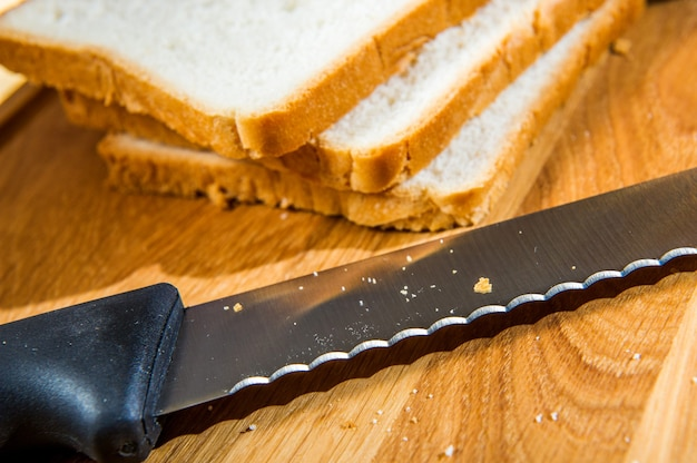 Holzschneidebrett mit geschnittenem weißbrot und messer auf holztisch