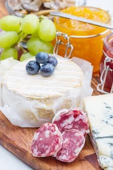 Holzschneidebrett mit käse, aufschnitt und marmelade