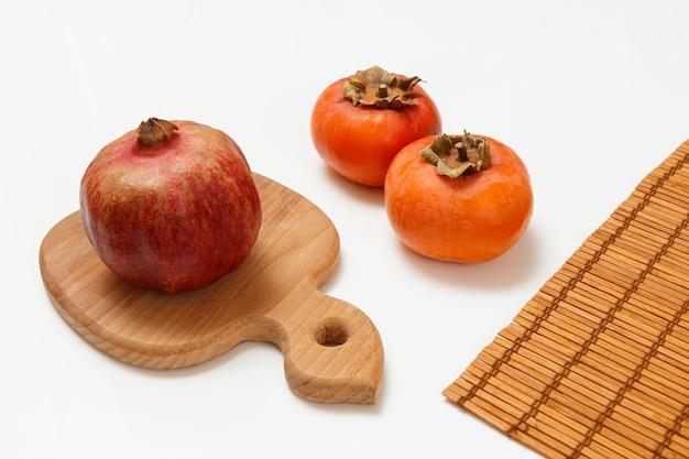 Holzschneidebrett mit reifem granatapfel, kakifrüchten und einer bambusserviette auf weißem hintergrund. bio-früchte.