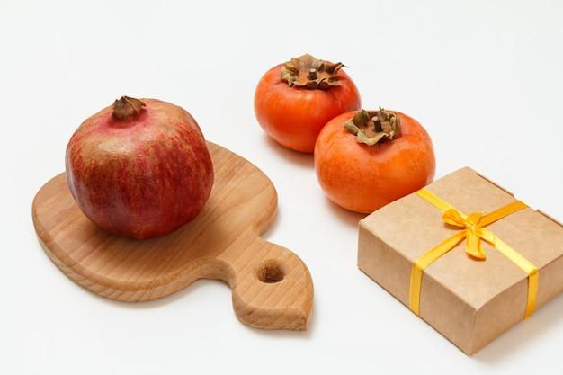 Holzschneidebrett mit reifen granatapfel- und kakifrüchten mit einer geschenkbox auf dem weißen hintergrund. bio-früchte.