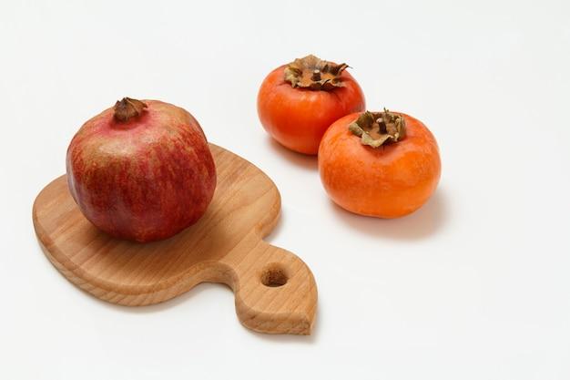 Holzschneidebrett, reifer granatapfel und kakifrüchte auf dem weißen hintergrund. bio-früchte.