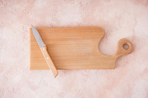 Holzschneidebrett und messer auf beigem hintergrund, platz für text. draufsicht.