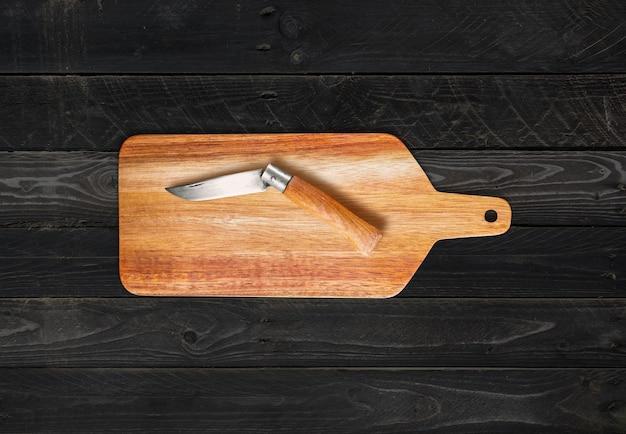 Holzschneidebrett und taschenmesser auf schwarzem holztischhintergrund