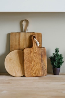 Holzschneidebretter in verschiedenen formen und ein kleiner weihnachtsbaum in einem topf