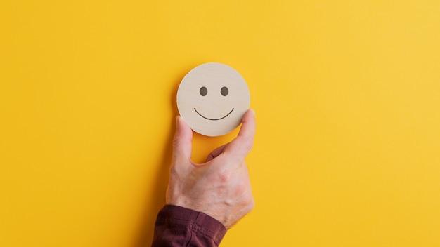 Holzschnittkreis mit lächelndem gesicht darauf