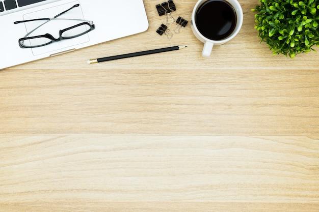 Holzschreibtisch mit laptop, kaffee und zubehör.