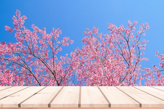 Holzschreibtisch oder holzboden für produktpräsentation mit rosa sakura-hintergrund