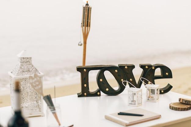 Holzschriftzug liebe steht auf tisch mit dekorativen laternen