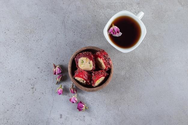 Holzschüssel mit köstlichen, in scheiben geschnittenen köstlichkeiten und eine tasse tee auf steinhintergrund.