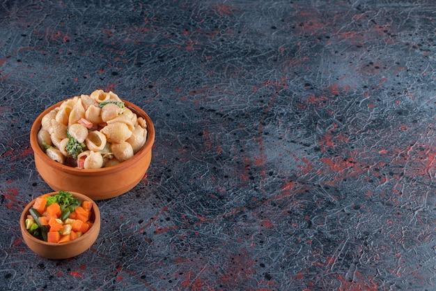 Holzschüssel mit köstlichen muschelnudeln und minisalat auf marmoroberfläche.