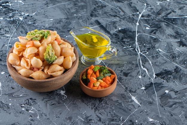 Holzschüssel mit leckeren muschelnudeln mit frischem salat auf marmoroberfläche.