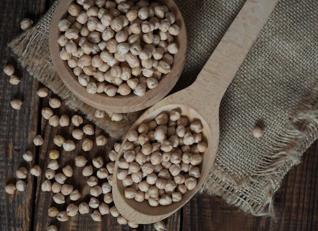 Holzschüssel und holzlöffel voller kichererbsen auf holzhintergrund. ansicht von oben.kichererbse