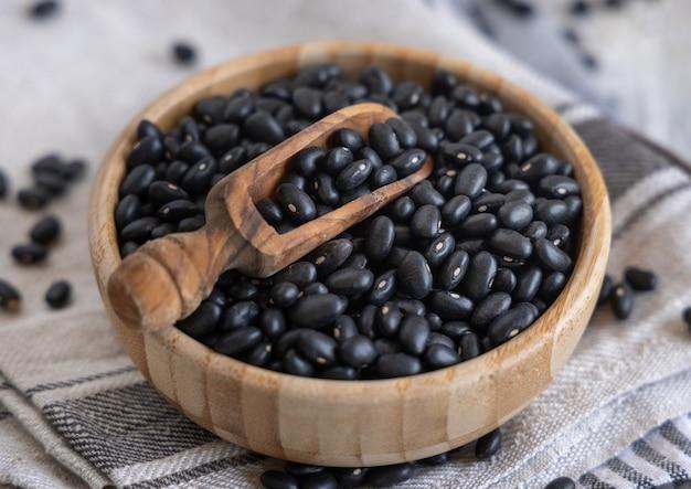 Holzschüssel voller getrockneter schwarzer bohnen mit einem holzlöffel auf küchentüchern auf einem holztisch hautnah. gesundes essen und vegetarisches konzept. traditionelle lateinamerikanische cousine-zutat
