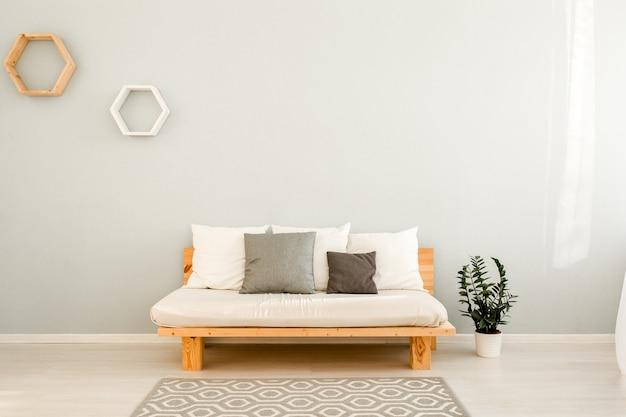 Holzsofa mit kissen im skandinavischen wohnzimmerstil mit rundem couchtisch und ficuspflanze