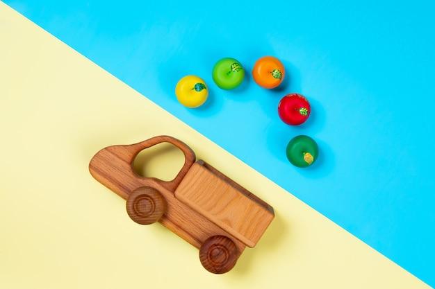 Holzspielzeug lkw mit äpfeln auf einem isolierten bunten lebendigen geometrischen hintergrund.