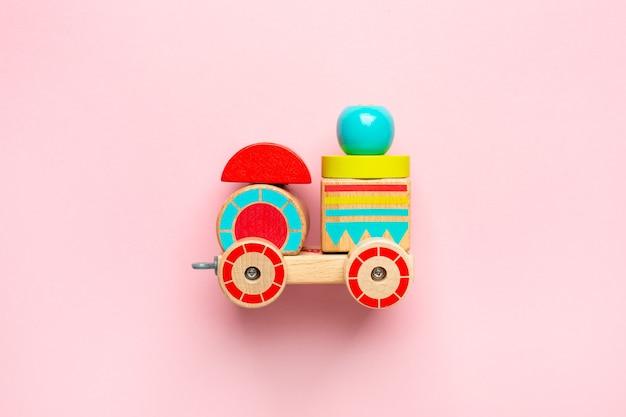 Holzspielzeugauto mit bunten blöcken auf rosa draufsicht
