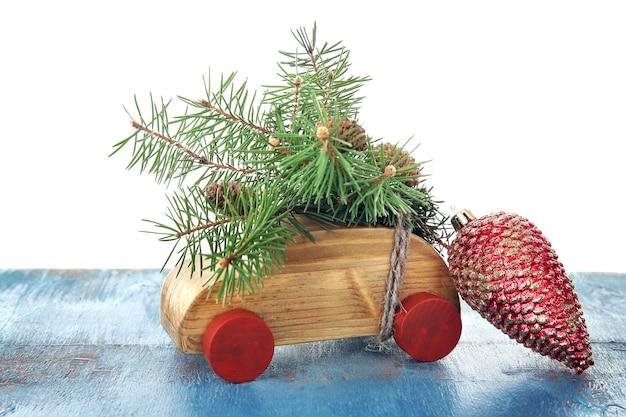 Holzspielzeugauto mit tannenzweigen und kegel auf einem tisch über weiß