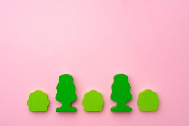 Holzspielzeugbäume und büsche auf rosa papier