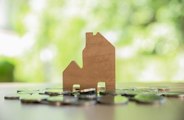 Holzspielzeughaus mit münzen auf holztisch