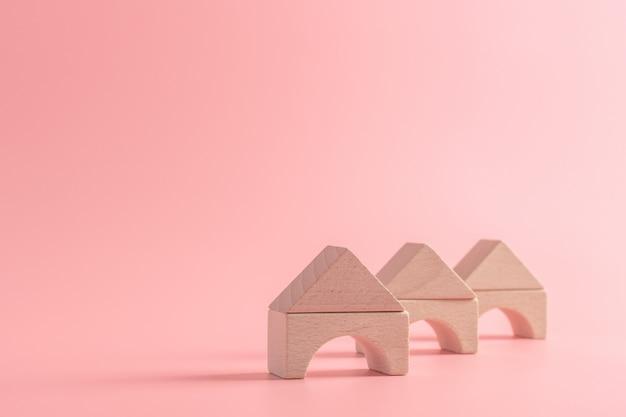 Holzspielzeughaus oder haus auf lokalisiertem rosa. sachversicherung, familientraumkonzept erstellen