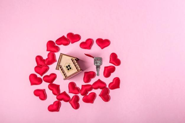 Holzspielzeughaus, rote herzen und schlüssel auf rosa wand. süßes haus oder geschenk für valentinstagkonzept. hypothekenkonzept. umweltfreundliches haus. kopieren sie platz für text
