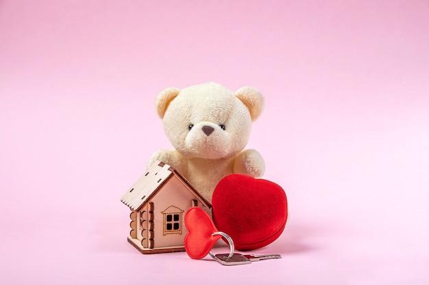 Holzspielzeughaus, rotes herz, ausgestopfter bär, schlüssel und schmuckschatulle auf rosa wand. süßes haus oder geschenk für valentinstagkonzept. hypothekenkonzept. kopieren sie den speicherplatz für textgbn