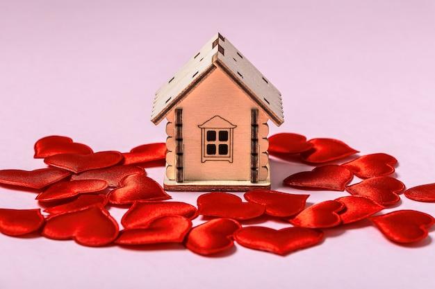 Holzspielzeughaus und rote herzen auf rosa wand. süßes haus oder geschenk für valentinstagkonzept. hypothekenkonzept. umweltfreundliches haus. platz für text kopieren '