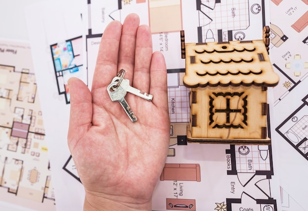 Holzspielzeughaus und schlüssel auf der handfläche. das konzept der renovierung, des kaufs oder des baus eines hauses.