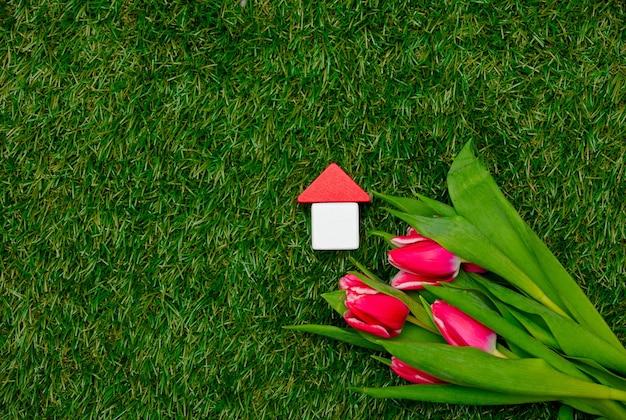 Holzspielzeughaus und tulpen auf grünem gras