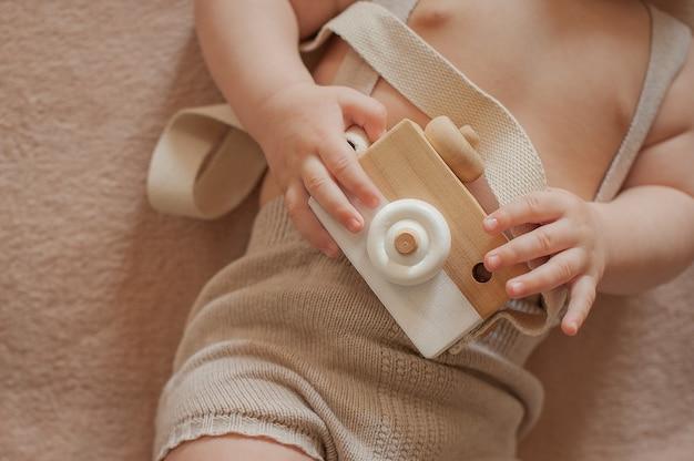 Holzspielzeugkamera in den händen eines babys