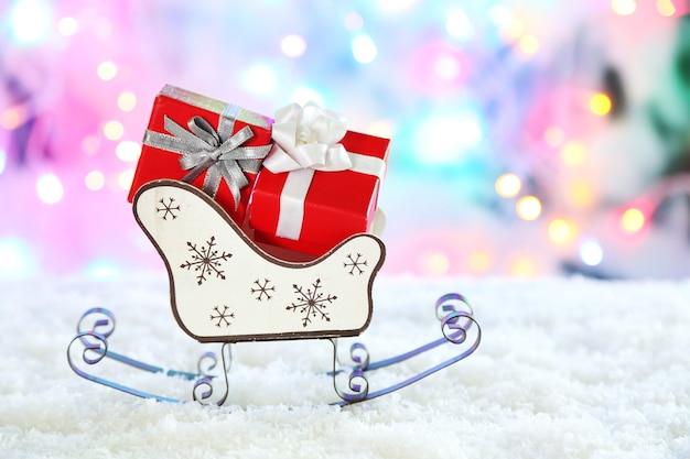 Holzspielzeugschlitten mit weihnachtsgeschenken auf glänzendem hintergrund