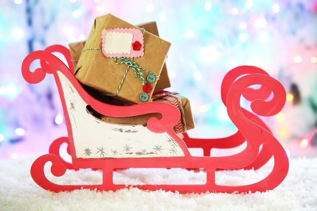 Holzspielzeugschlitten mit weihnachtsgeschenken auf glänzender oberfläche