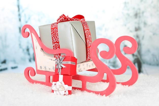 Holzspielzeugschlitten mit weihnachtsgeschenken auf naturoberfläche