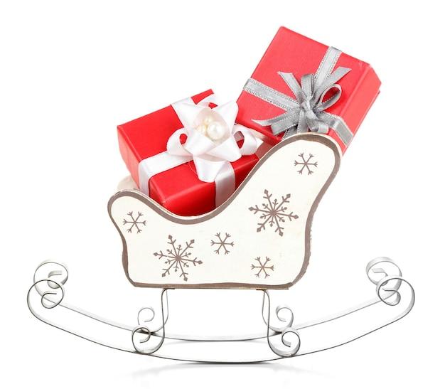 Holzspielzeugschlitten mit weihnachtsgeschenken, isoliert auf weiß