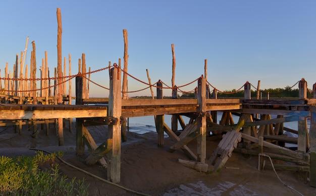 Holzstangen und pontonbeleuchtung durch sonne bei sonnenuntergang im atlantik