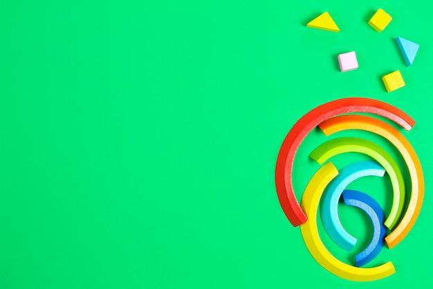 Holzstapelspielzeugregenbogen und bunte blöcke auf grünem hintergrund. draufsicht