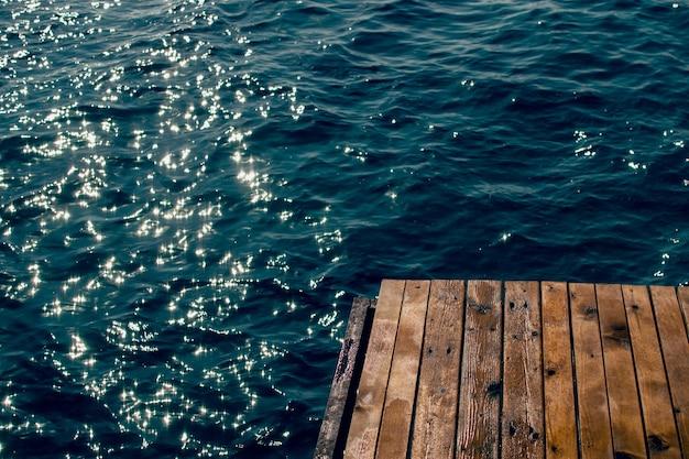 Holzsteg am blauen wasser des meeres im sonnenlicht