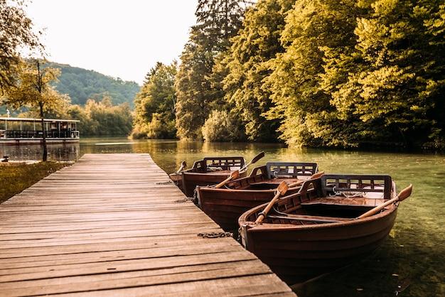 Holzsteg und boote auf dem see.
