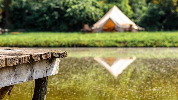 Holzsteg zum ausruhen in der nähe eines sees mit zelt im hintergrund beim glamping. natur, grün ringsum