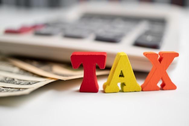 Holzsteuerwort auf banknote und taschenrechner und buchbank. konzept der steuerzahlung, leistung oder obligatorischen finanziellen belastung.